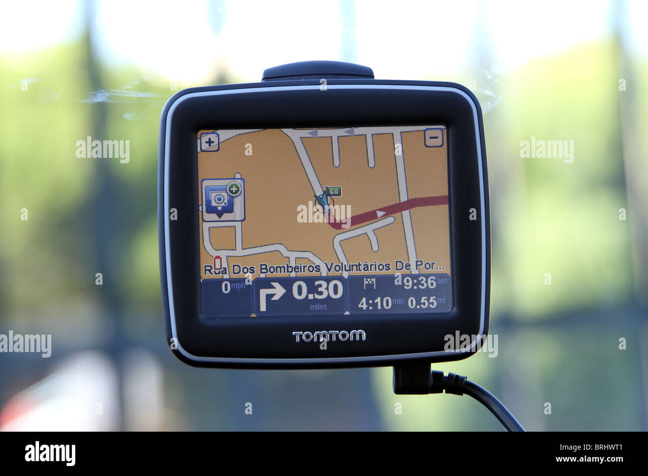 Satellite Navigation device in action and attached to a car windscreen - Stock Image