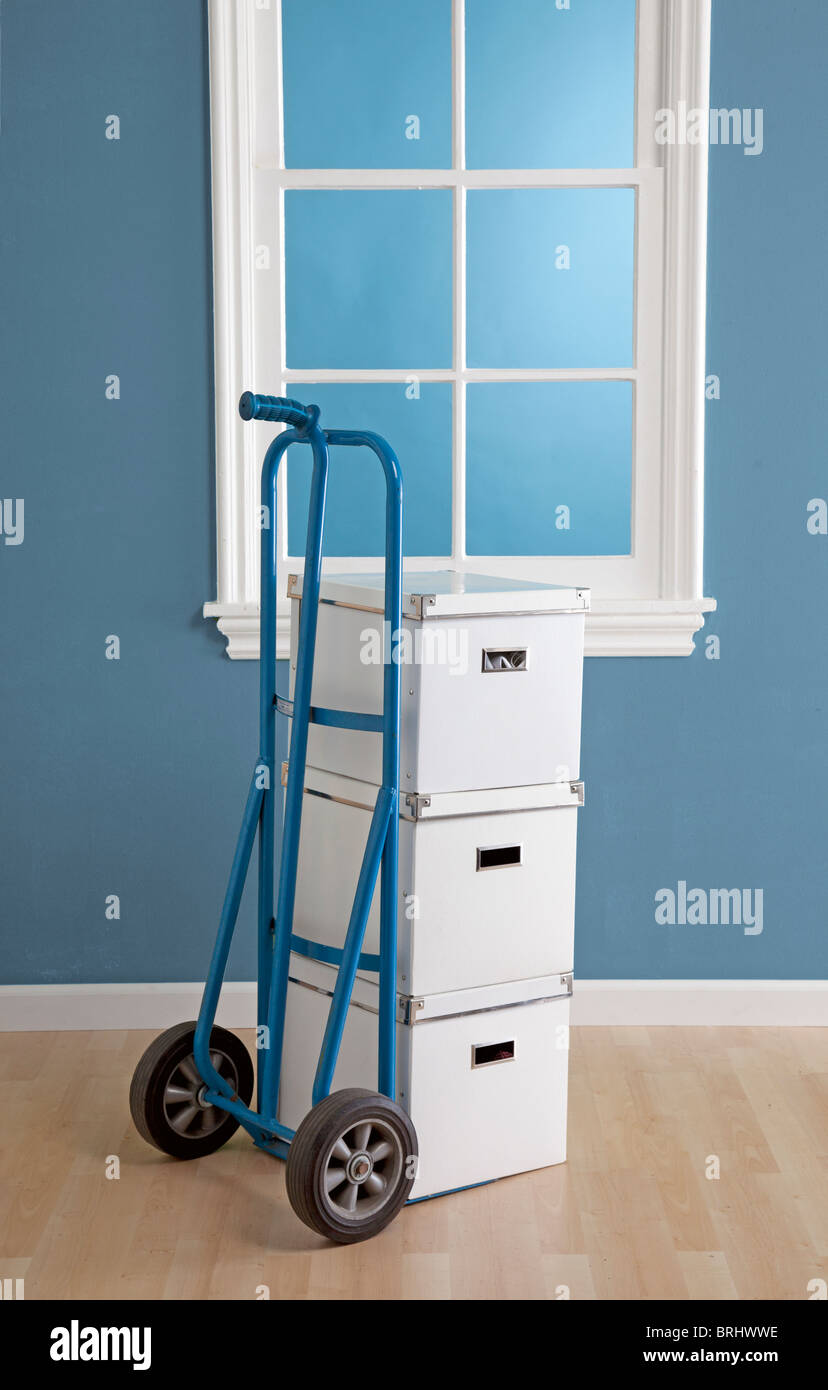 dolly with boxes stacked for moving in room - Stock Image