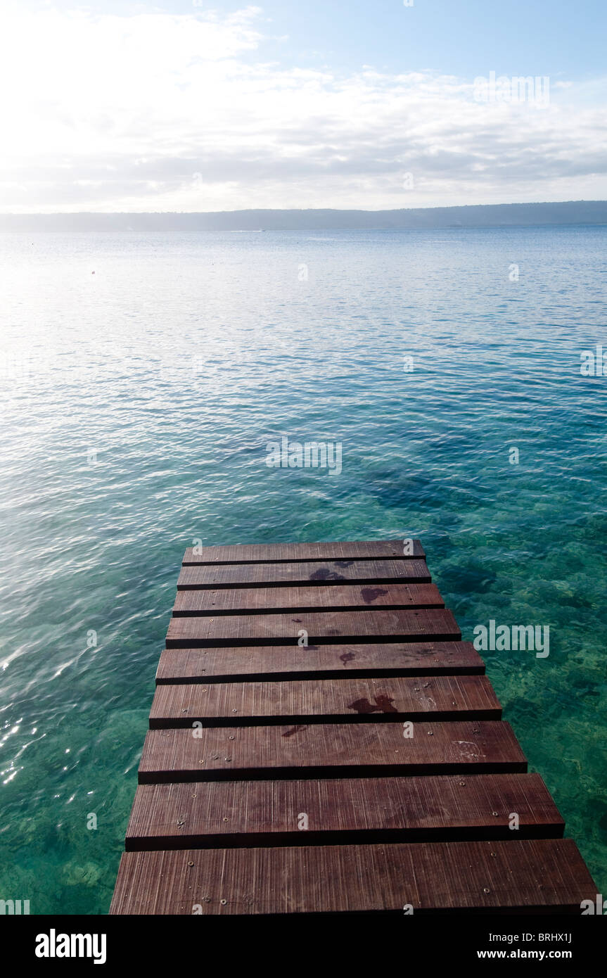 wooden pier over looking ocean with sunset, Vanuatu - Stock Image