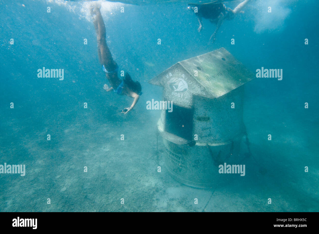 Girls diving towards the worlds only Underwater post office, about 20 meters of Hideaway island, South Pacific ocean, - Stock Image