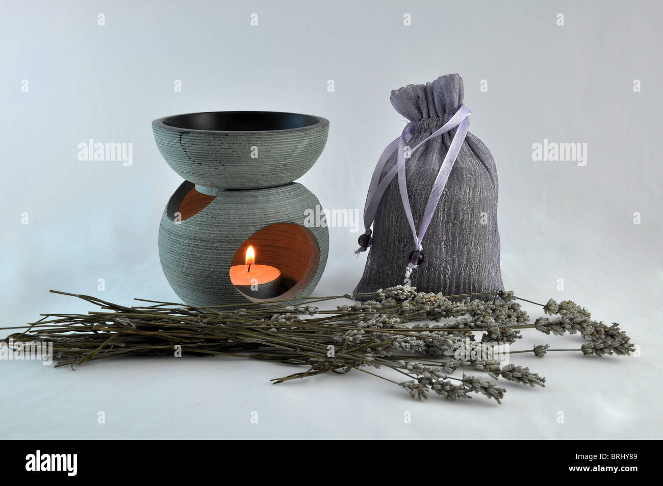 Lavender candle burner , and burning candle with dried lavender on a