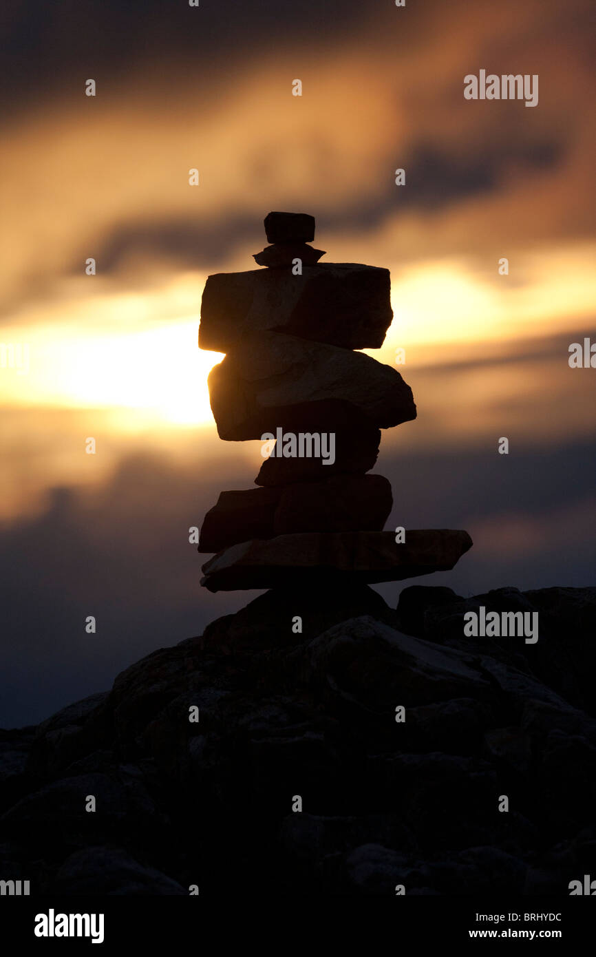 Sunset with a stone inukshuk in the foreground at Cape Bonavista, Newfoundland, Canada - Stock Image