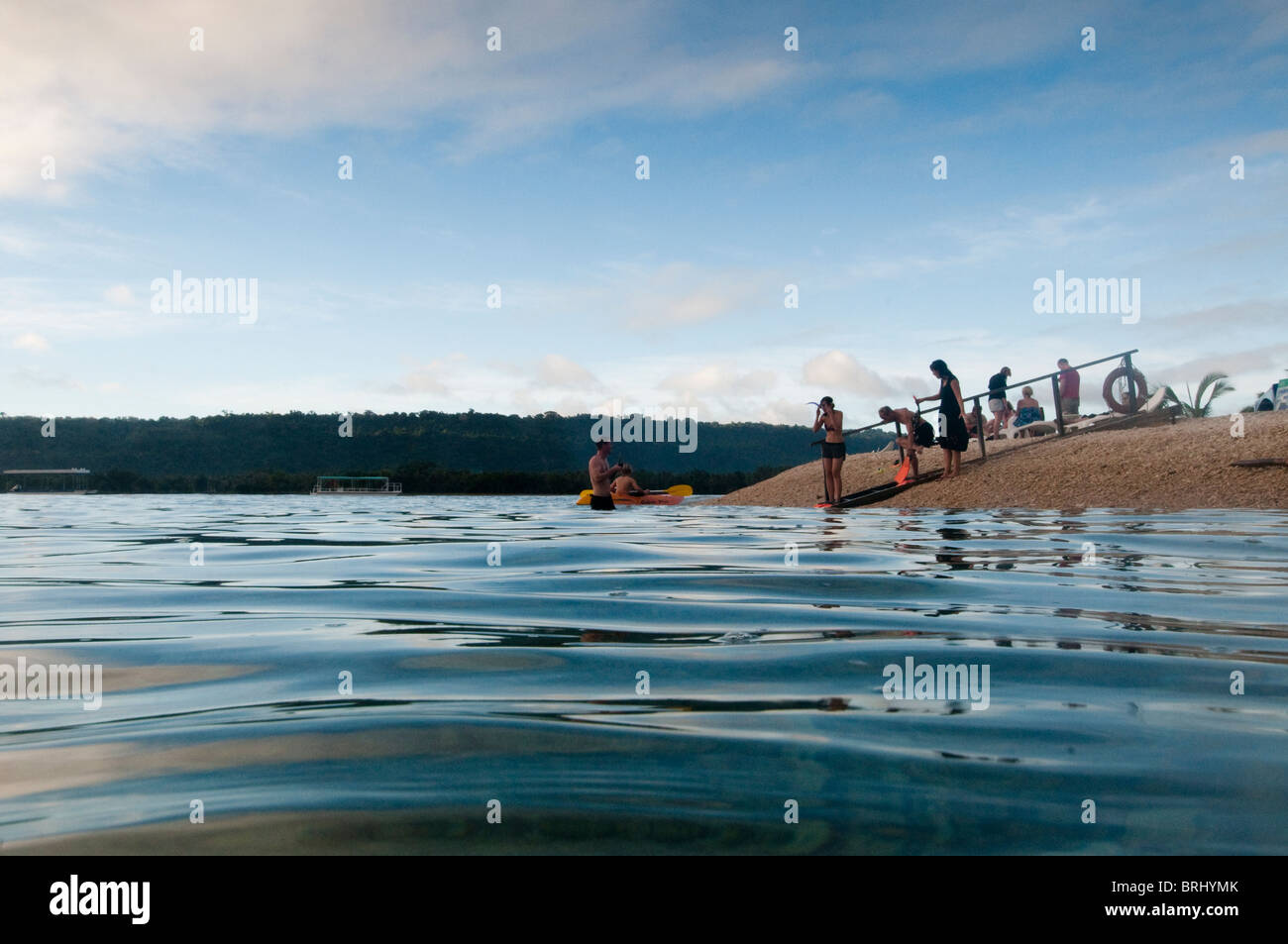 Family at waters edge on hideaway island, about to go snorkeling. - Stock Image