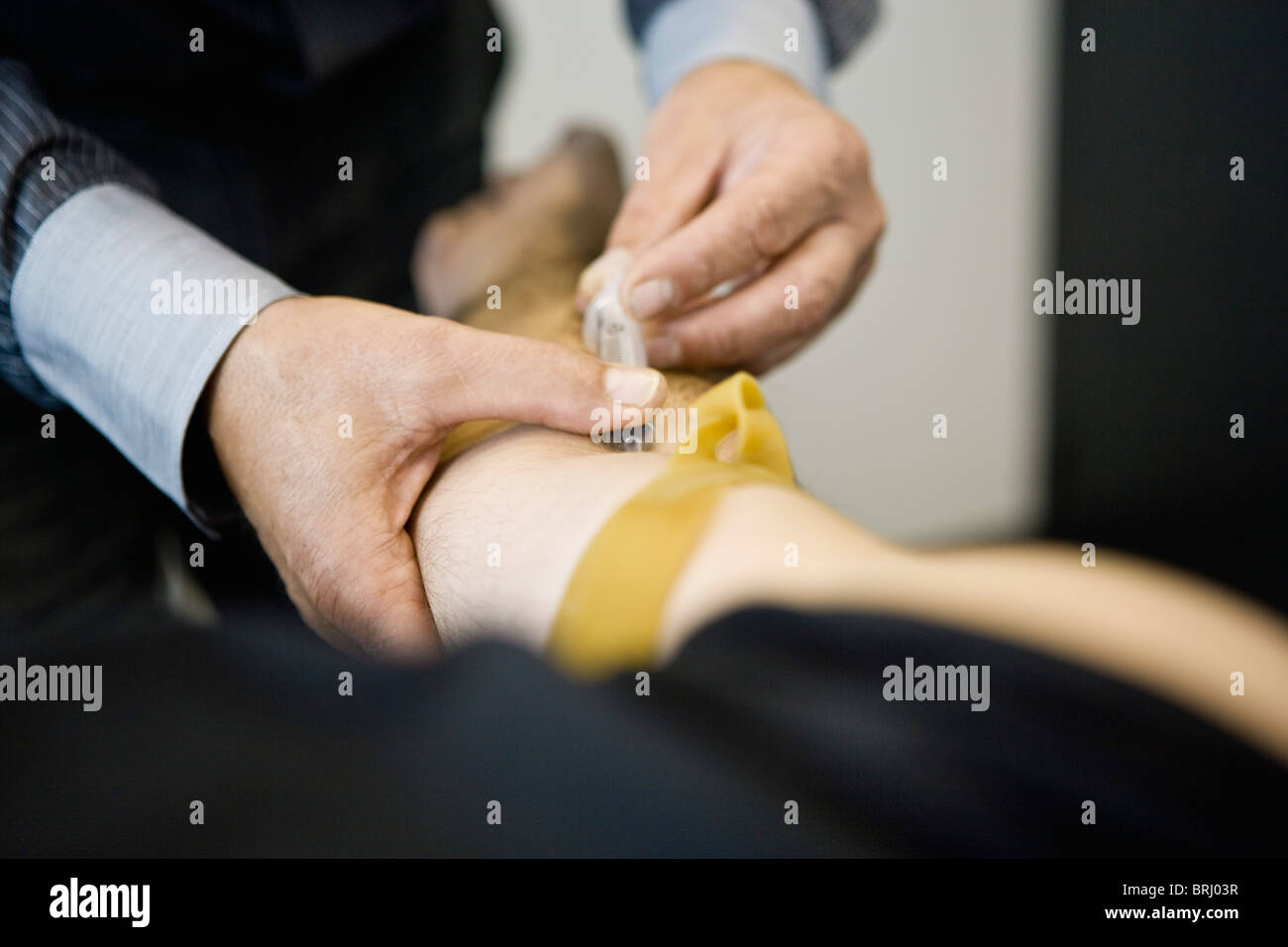Doctor giving patient an injection, cropped - Stock Image