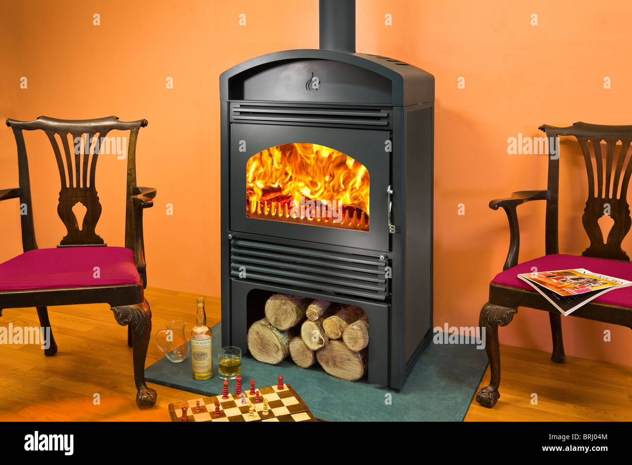 A Woodfire C18 wood burning stove with log store below - Stock Image