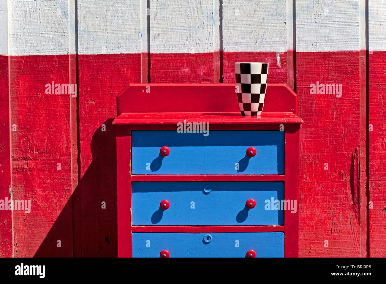 Checker vase on red drawers - Stock Image