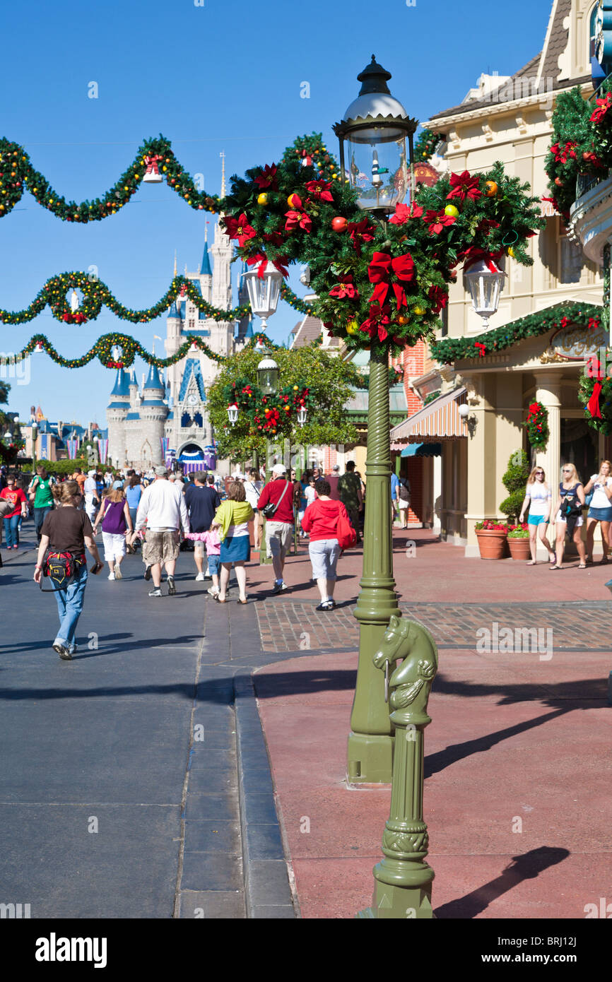 Mickey Mouse head logo in greenery and red bows decorates a lamp post along Main Street in Disney's Magic Kingdom - Stock Image