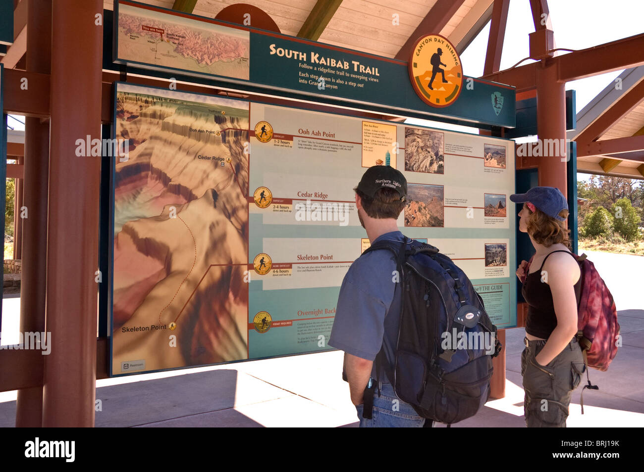 Arizona, Grand Canyon National Park, Grand Canyon Village, visitors looking at park trail sign - Stock Image