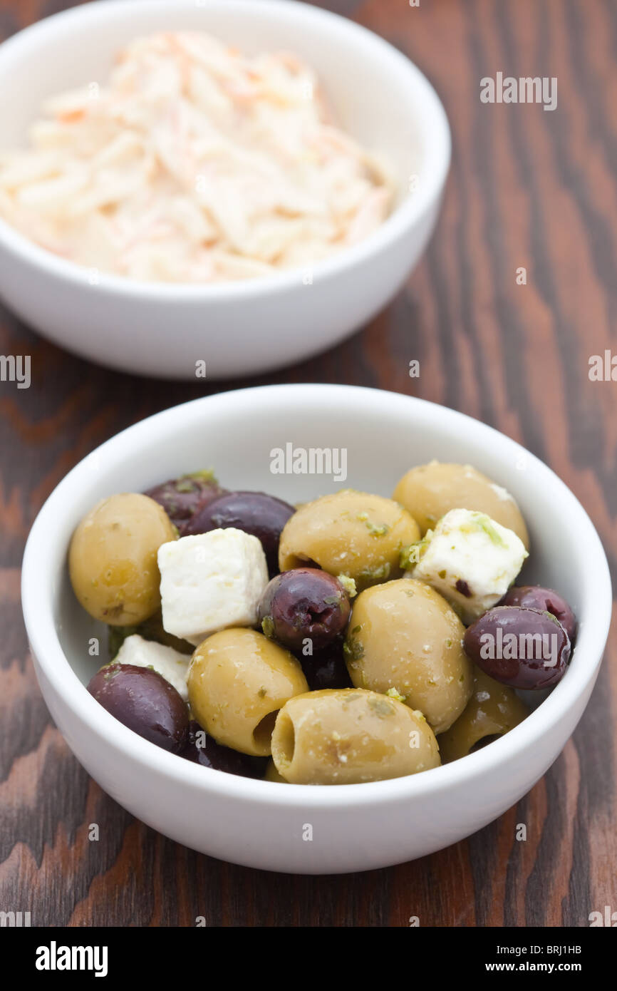 Appetiser of green and kalmata olives with feta cheese in a white bowl with coleslaw in the background - Stock Image