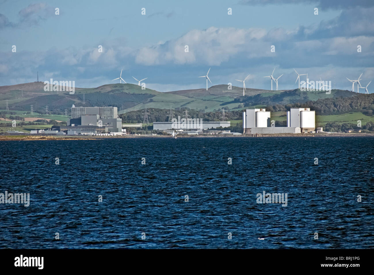 Hunterston Nuclear Power Station seen from the Firth of Forth with wind turbines behind on the hills - Stock Image
