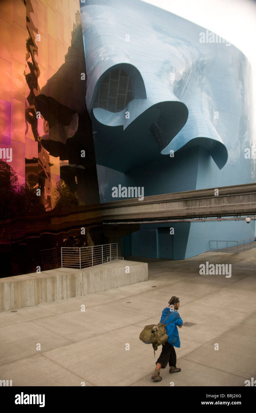 Homeless man walks past Experience Music Project Science Museum building architect Frank Gehry in Seattle Washington - Stock Image