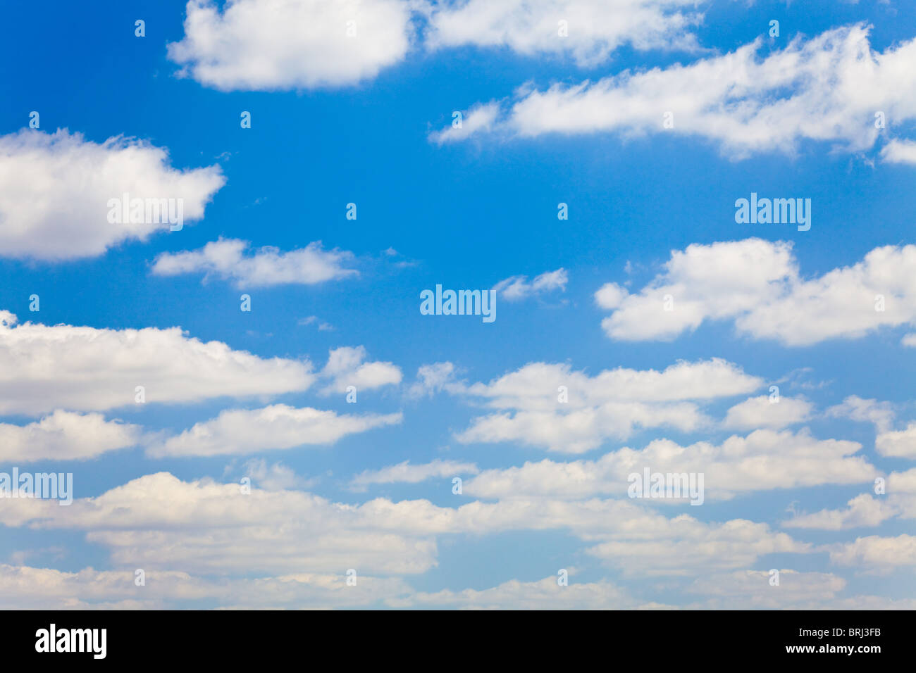 blue sky with white fluffy clouds background - Stock Image