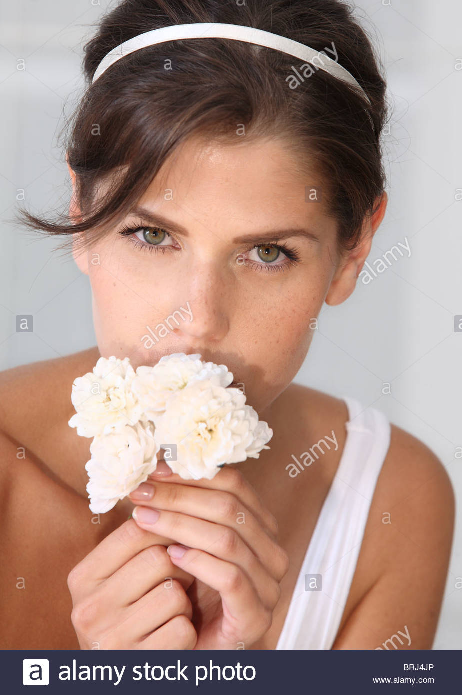 portrait of brunette woman with roses in hands Stock Photo