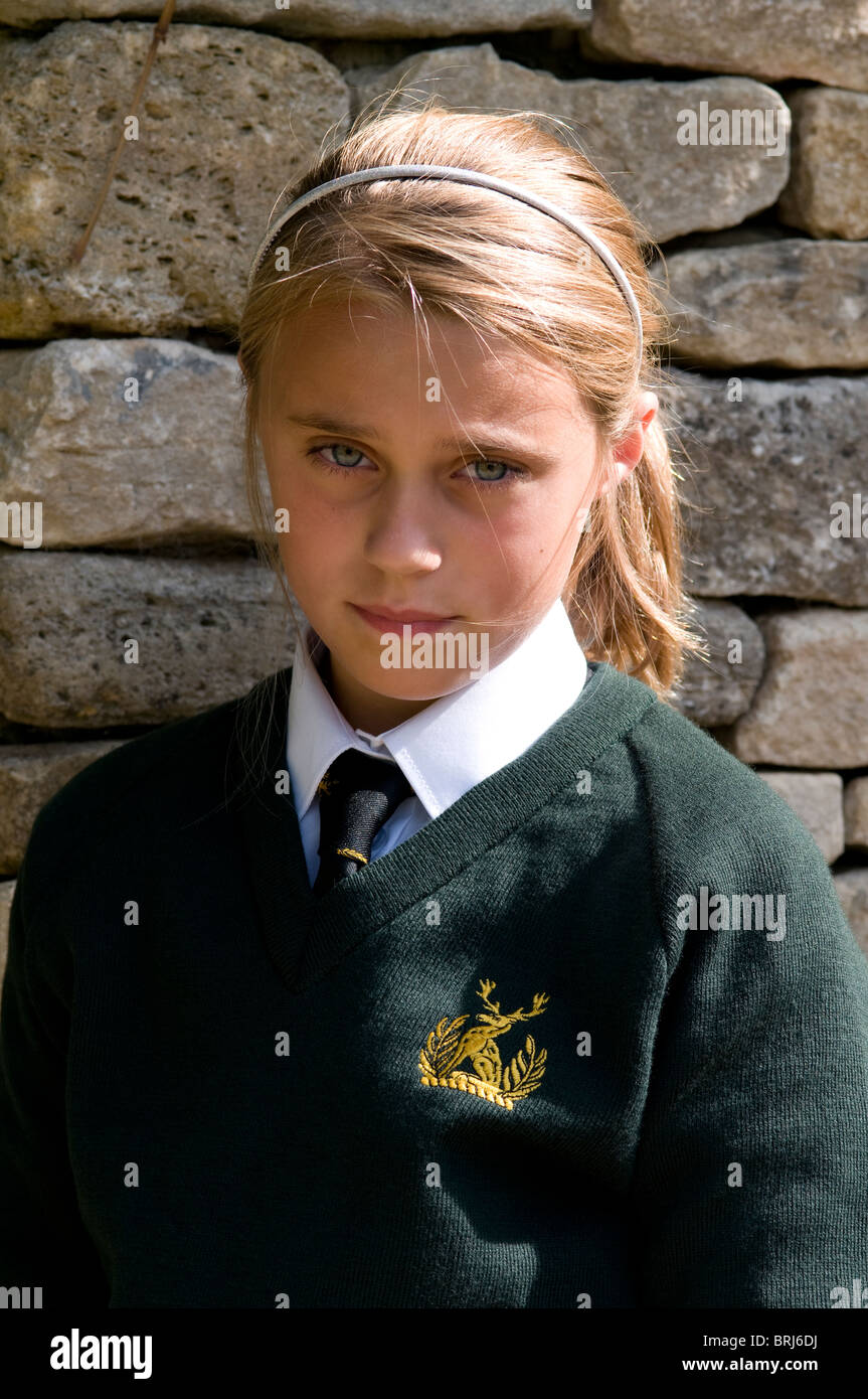 Portrait of a schoolgirl wearing school uniform looking apprehensive - Stock Image