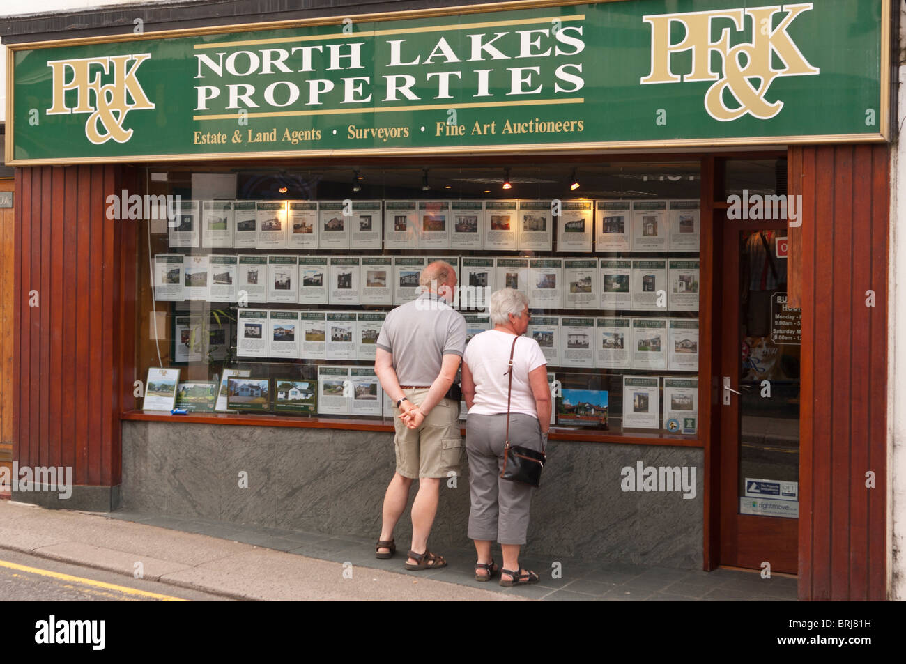 A couple viewing the North Lakes Properties estate agents window at Keswick , Cumbria , England , Great Britain - Stock Image