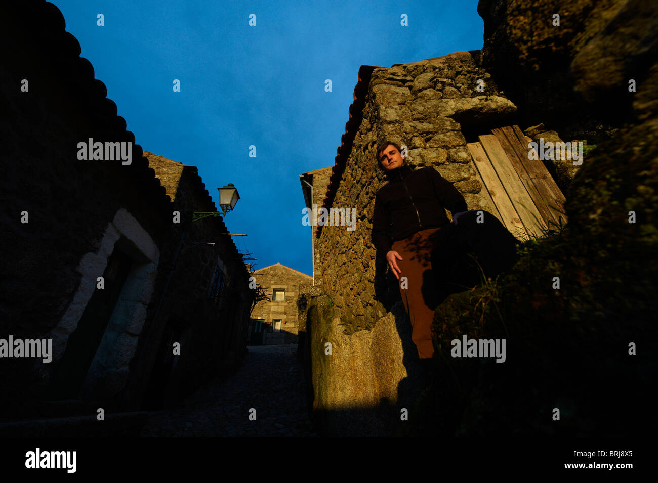 Man in front of traditional stone houses in the village of Monsanto, Portugal Stock Photo