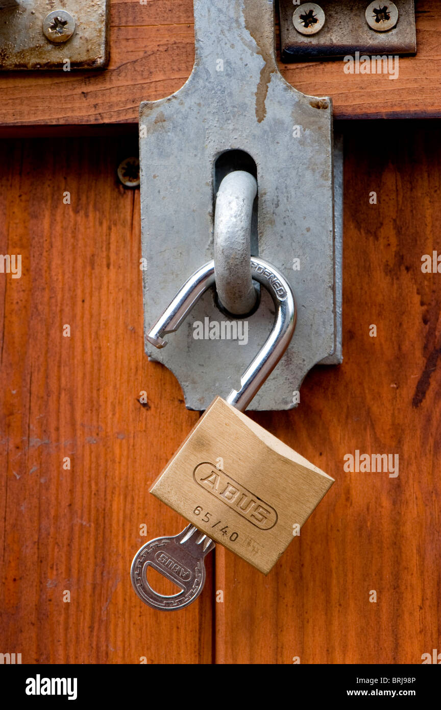 Padlock and bolt on a wooden door - Stock Image