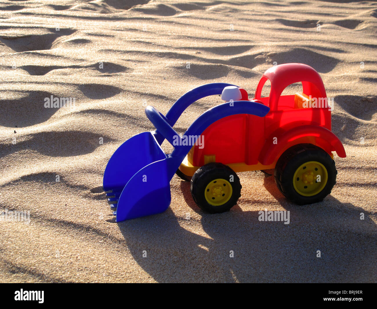Brightly coloured plastic toy truck on sandy beach - Stock Image