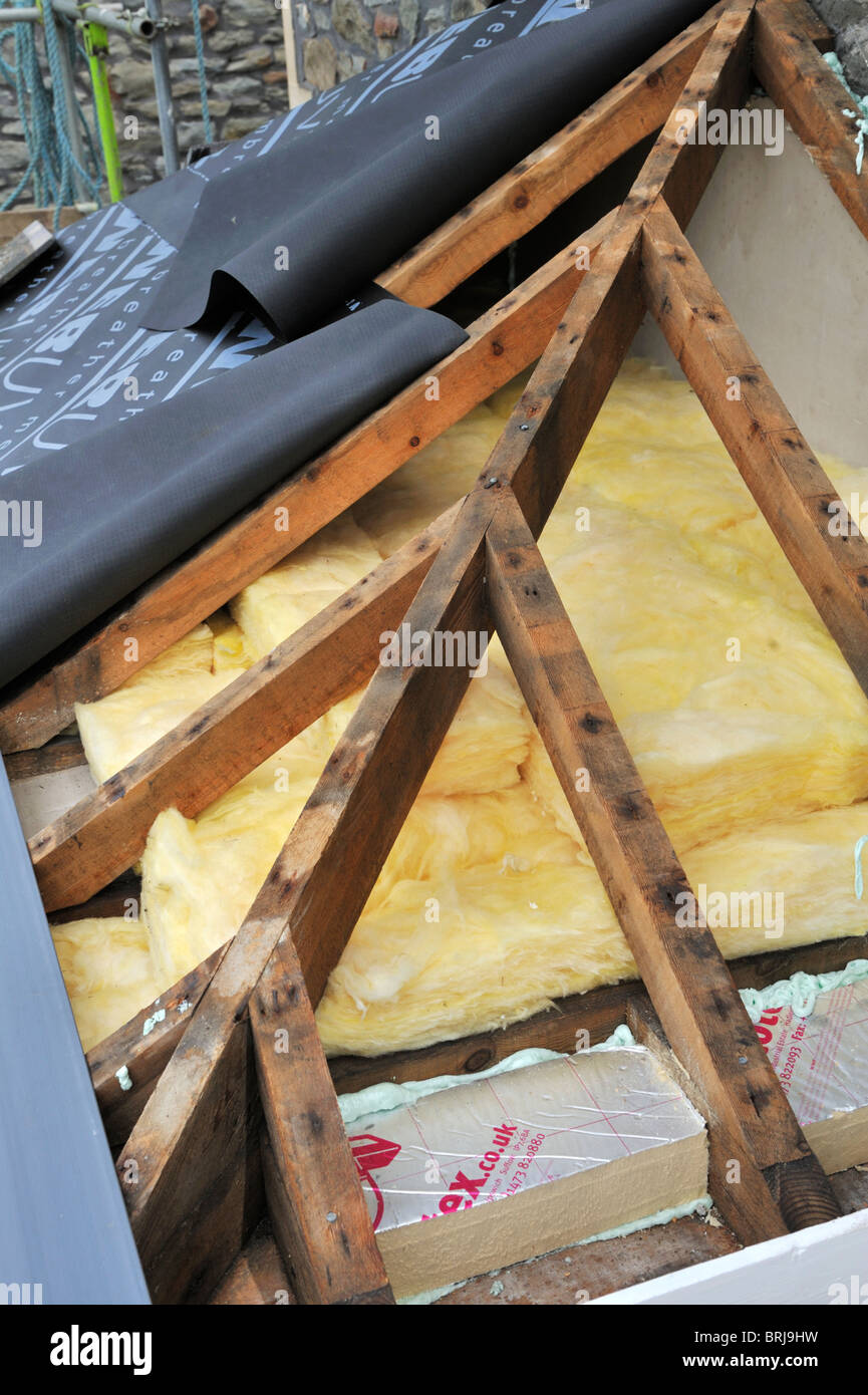 Bay window timber 'hip roof' trusses and fibreglass insulation seen from outside during refurbishment - Stock Image