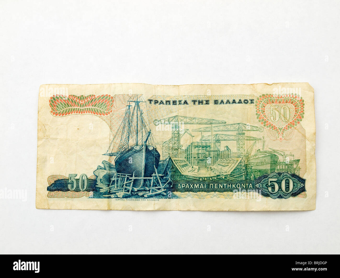 A Greek 50 Drachma bank note dated October 1964 on a white background. Back with shipyard picture  - Stock Image