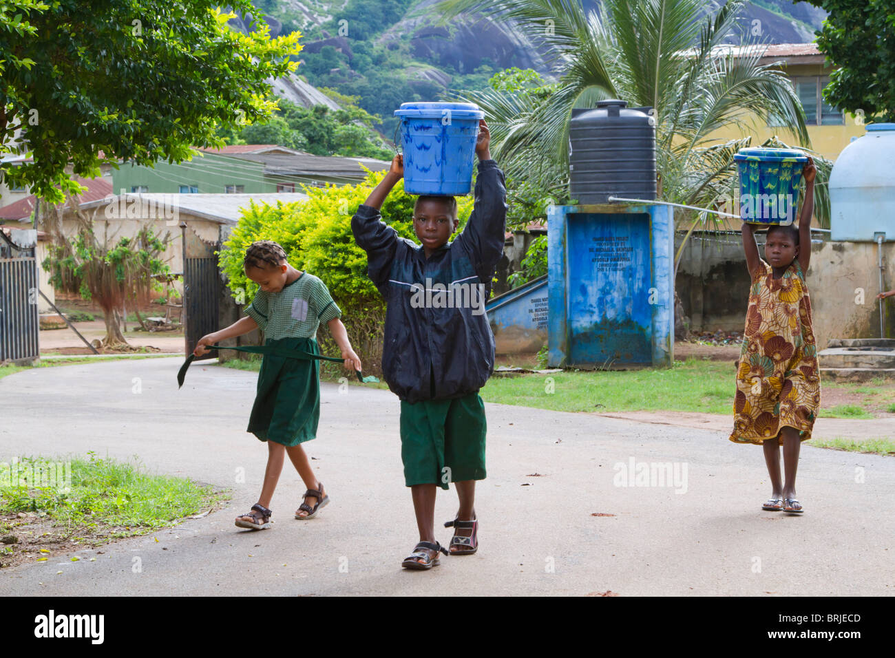 African children bearing buckets of water on their heads. - Stock Image