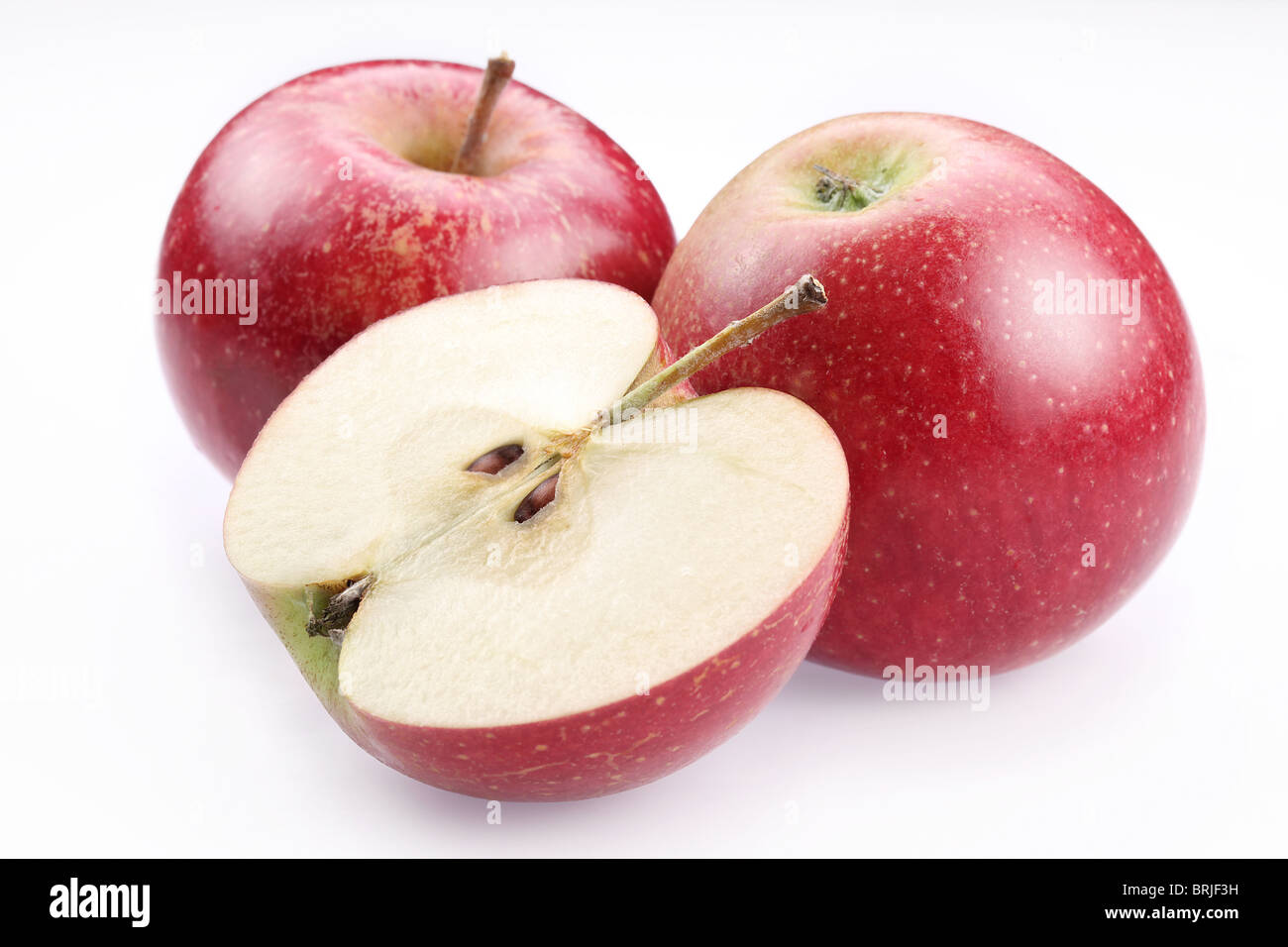 Red apple and a half of apple. Isolated on a white background. - Stock Image
