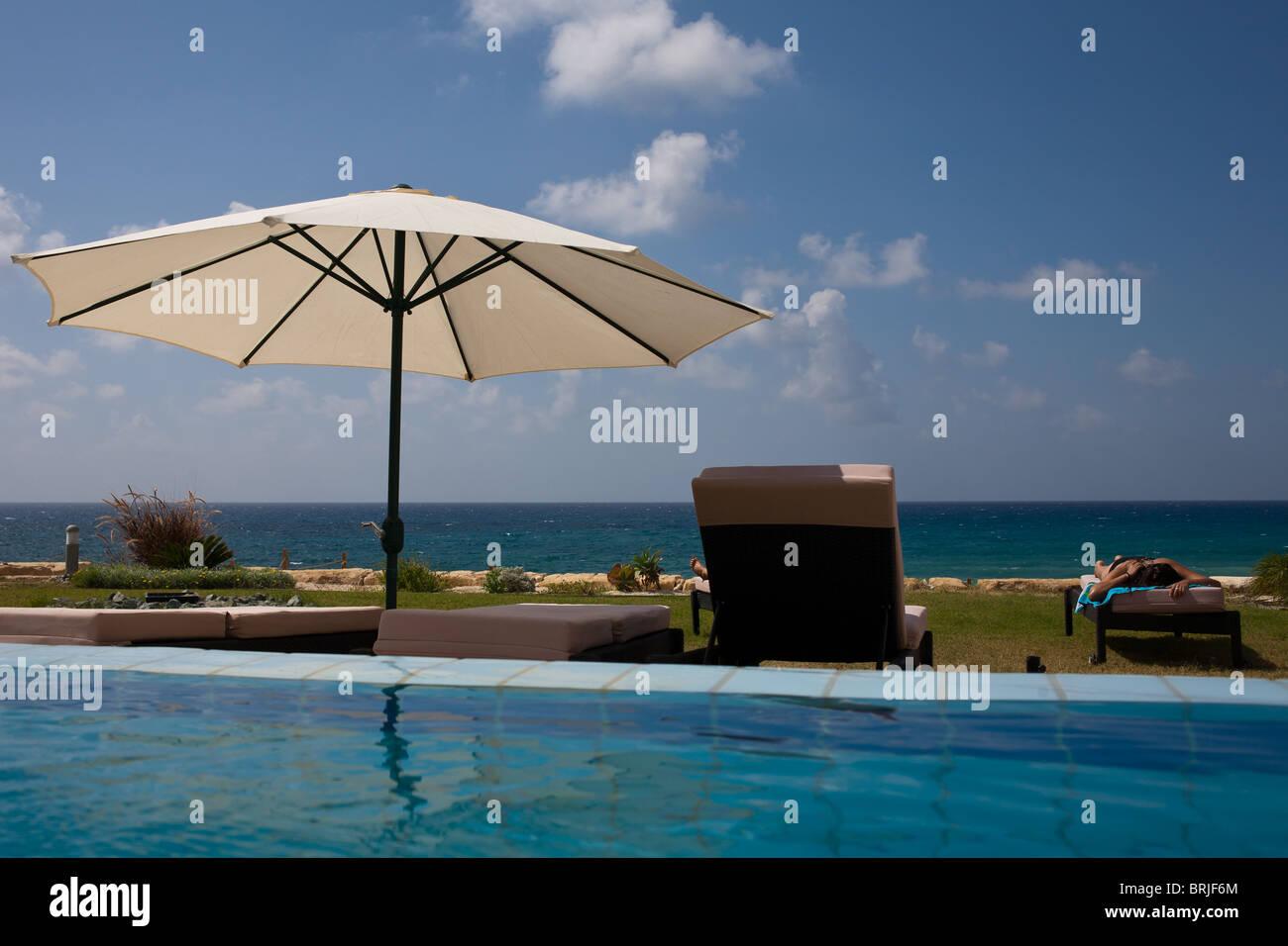 Swimming pool, parasol and Mediterranean Sea - Stock Image