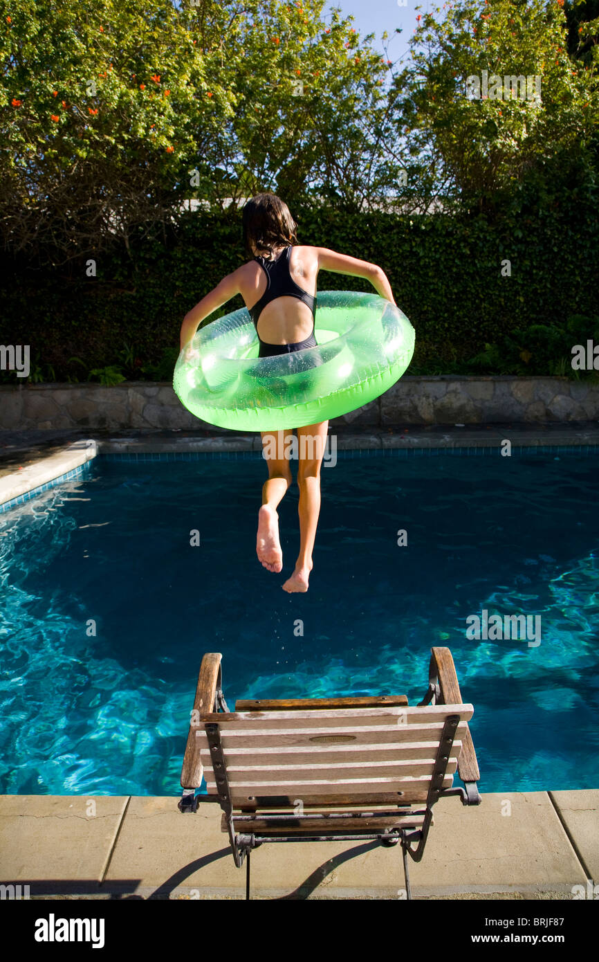 Girl with inner tube jumping into swimming pool - Stock Image