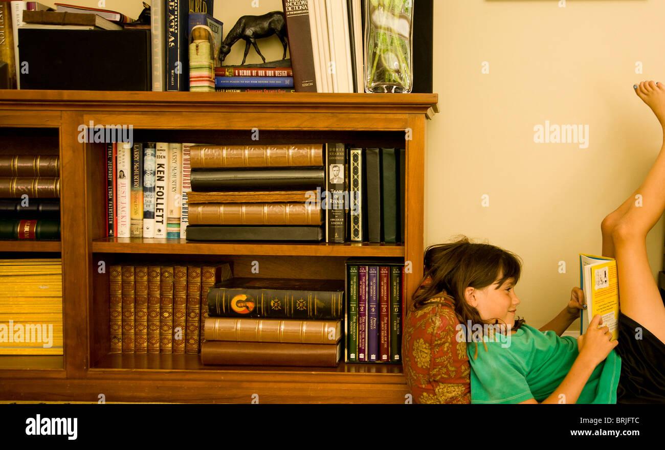 Girl beside bookshelf reading a book - Stock Image