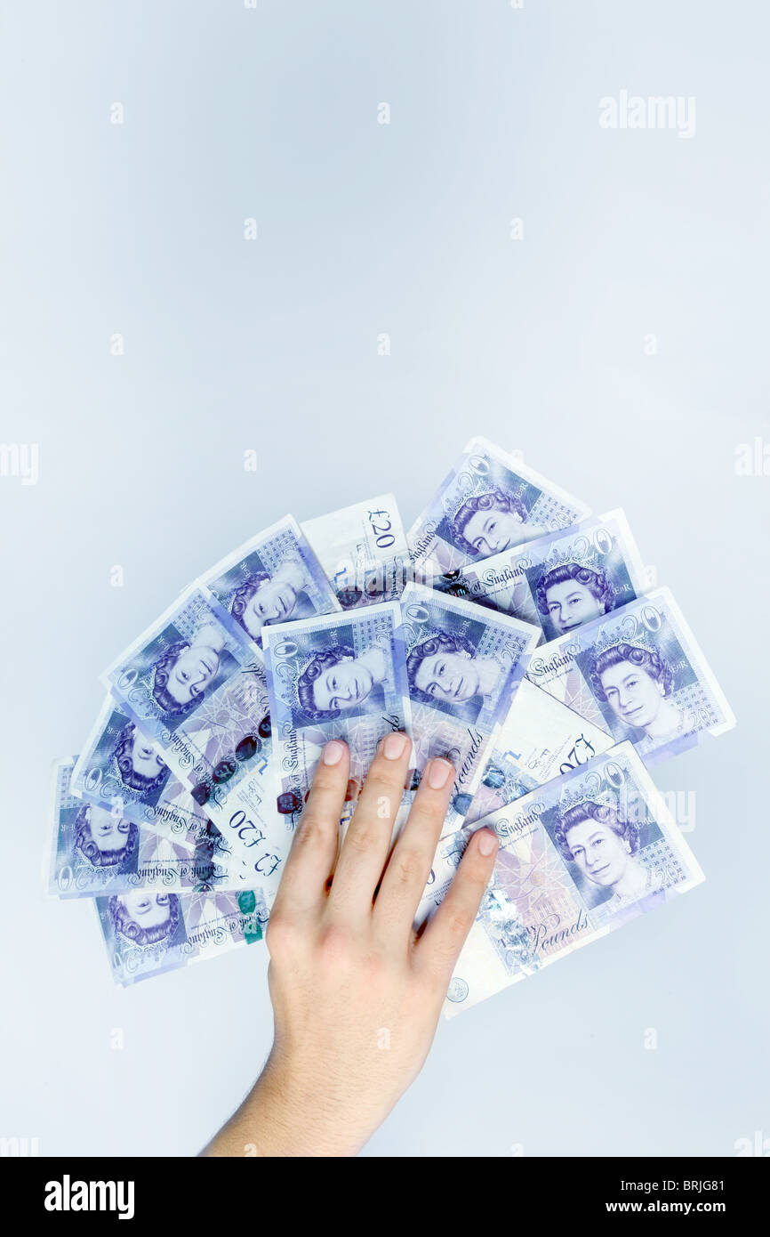 Hand holding £20 - Stock Image