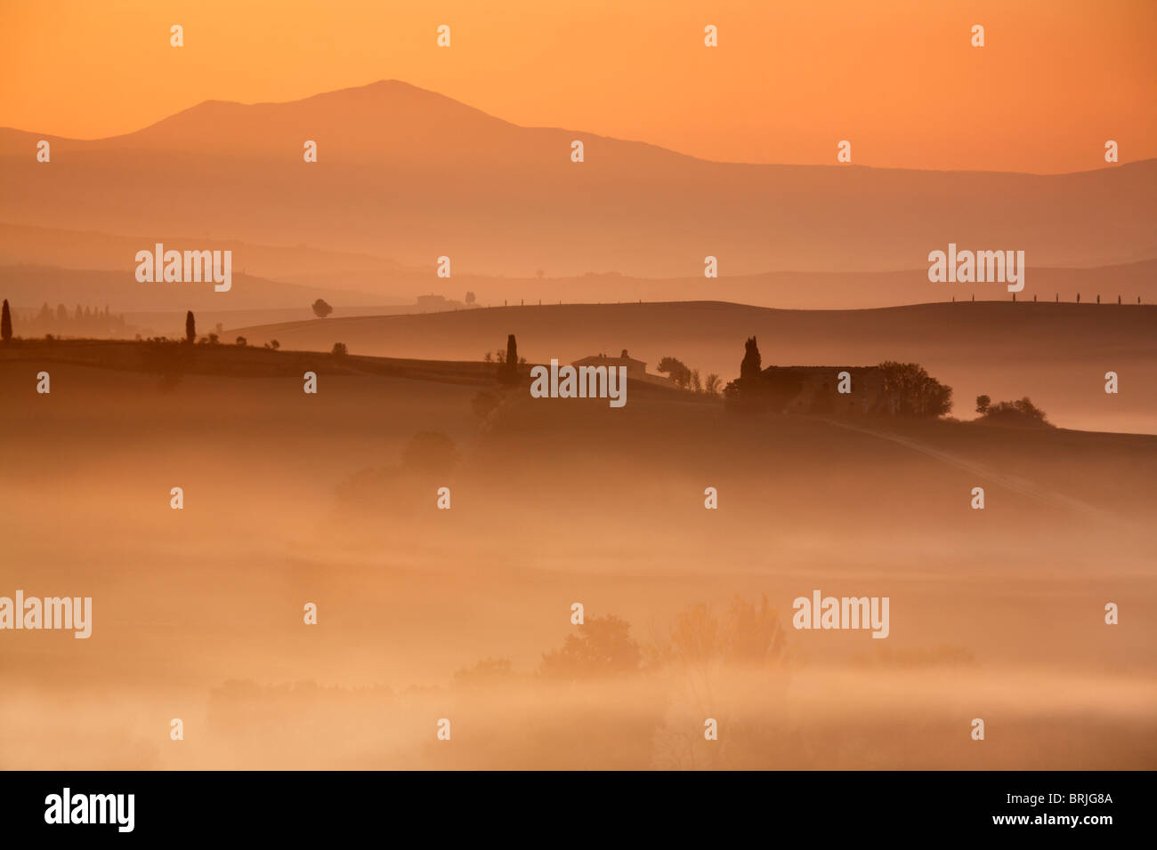 Pre-dawn light paints the misty landscape of the Val D'Orcia in brilliant orange & red hues beneath the - Stock Image
