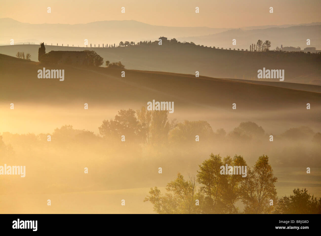 Sunrise light warms the misty valleys around Pienza in the Val D'Orcia region of Tuscany, Italy - Stock Image
