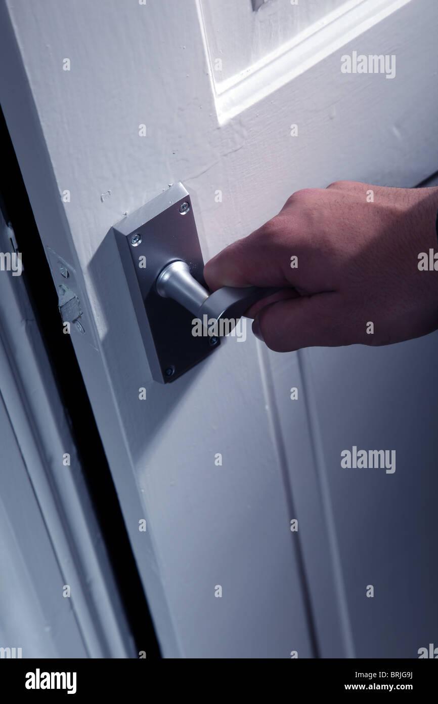 Male hand turning an internal door handle - Stock Image
