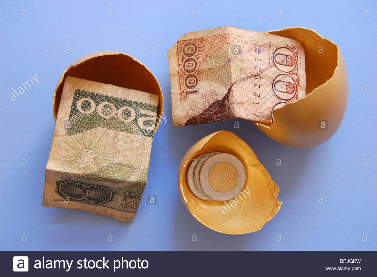 closeup overhead tabletop view three gold golden egg shells containing paper money currency depicting the savings - Stock Image