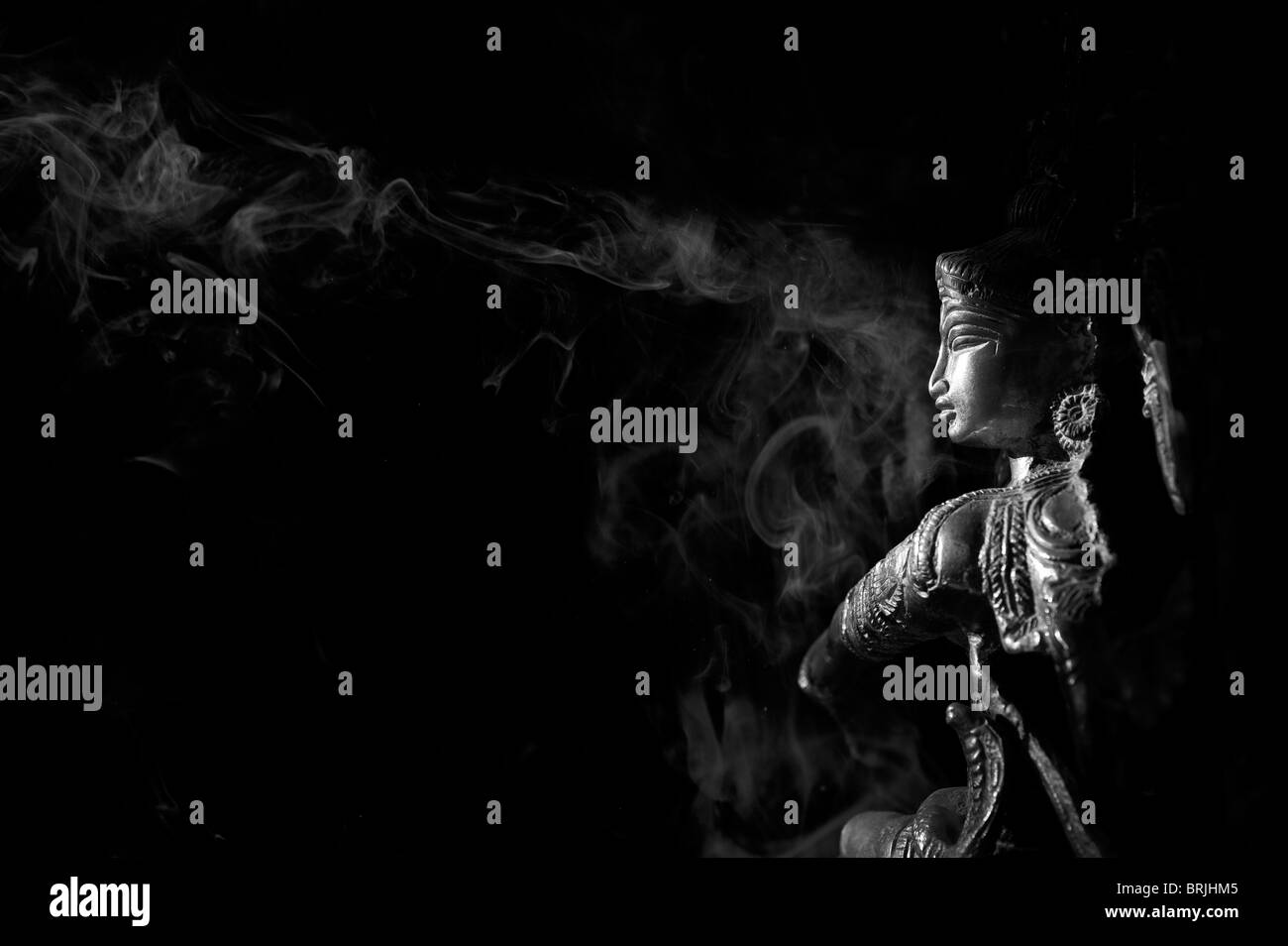 Dancing lord Shiva statue. Nataraja with incense smoke against black background. India. Black and White - Stock Image