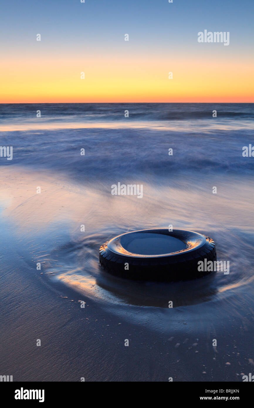 Discarded tyre dumped on a beach. - Stock Image