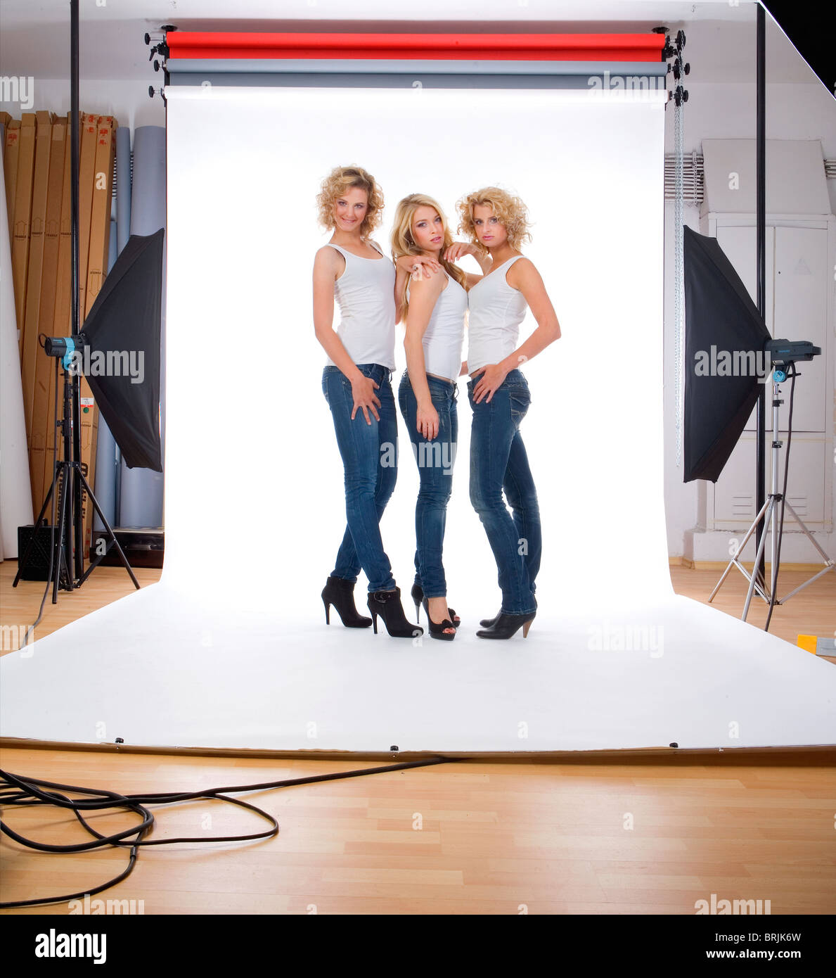 three young female models in casual clothing standing in photographer studio - Stock Image