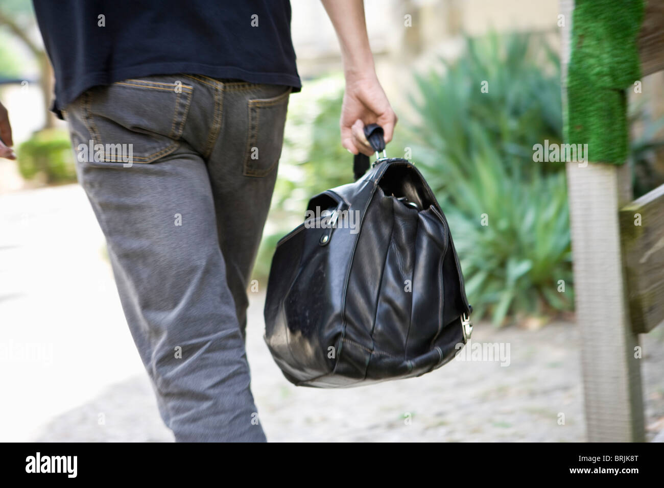 Man carrying bag, rear view Stock Photo