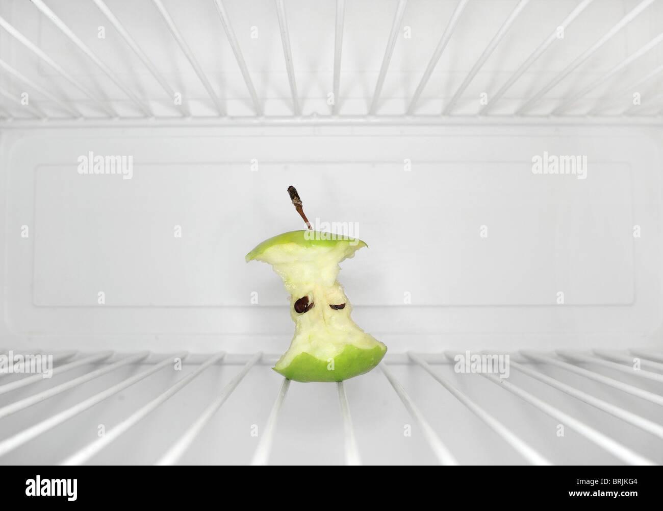 Single apple core sitting on shelf inside refrigerator - Stock Image