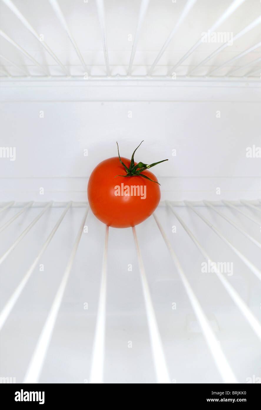 Single tomato sitting on shelf inside refrigerator Stock Photo