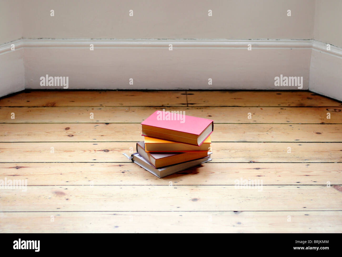 Books stacked on hardwood floor - Stock Image