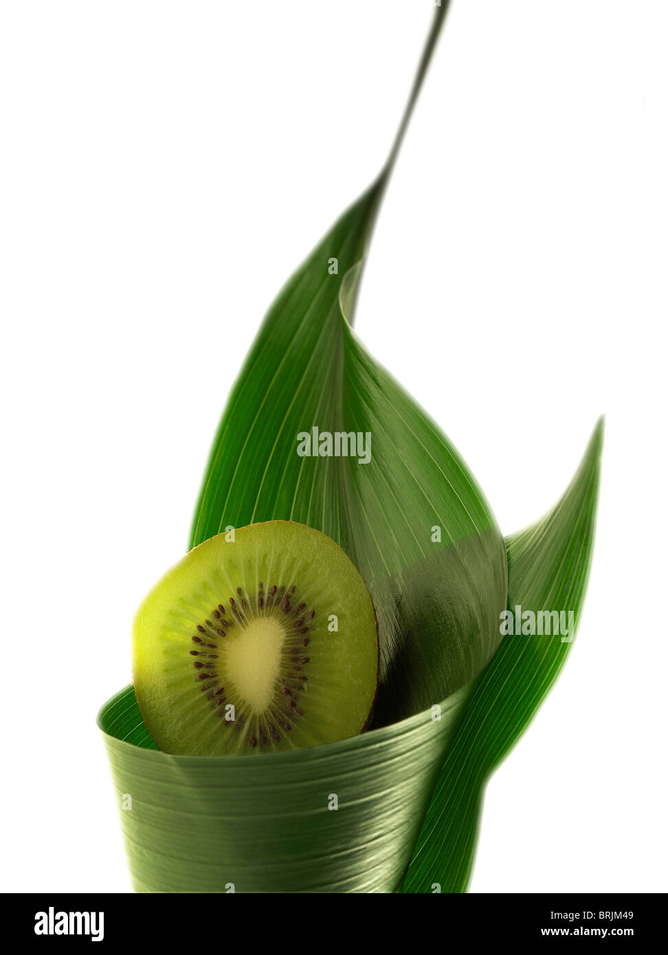 Sliced kiwi wrapped in leaf - Stock Image
