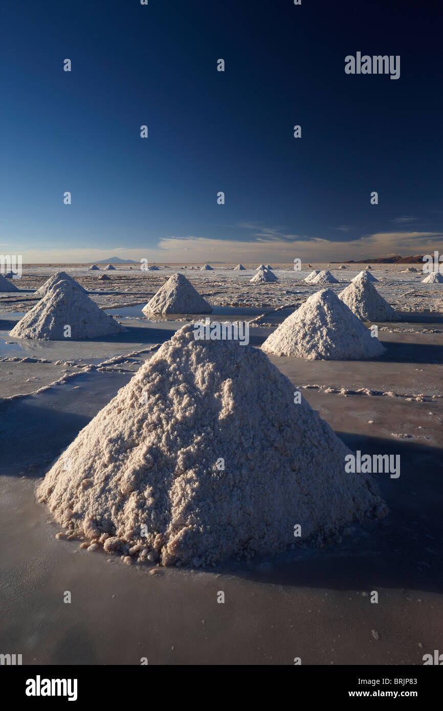 piles of salt on the Salar de Uyini at dusk, Bolivia - Stock Image