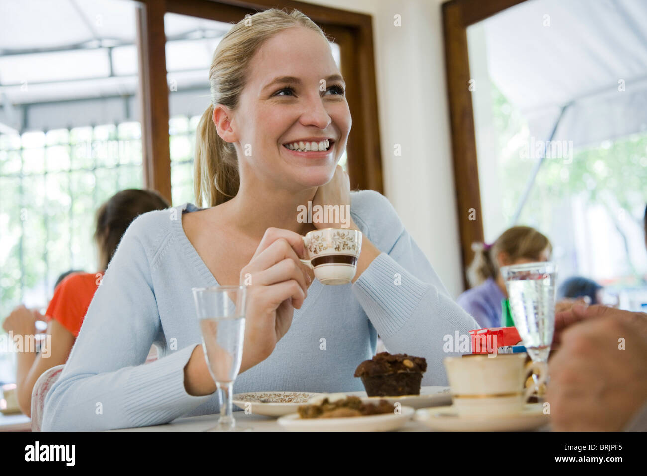 Young woman drinking coffee at cafe - Stock Image