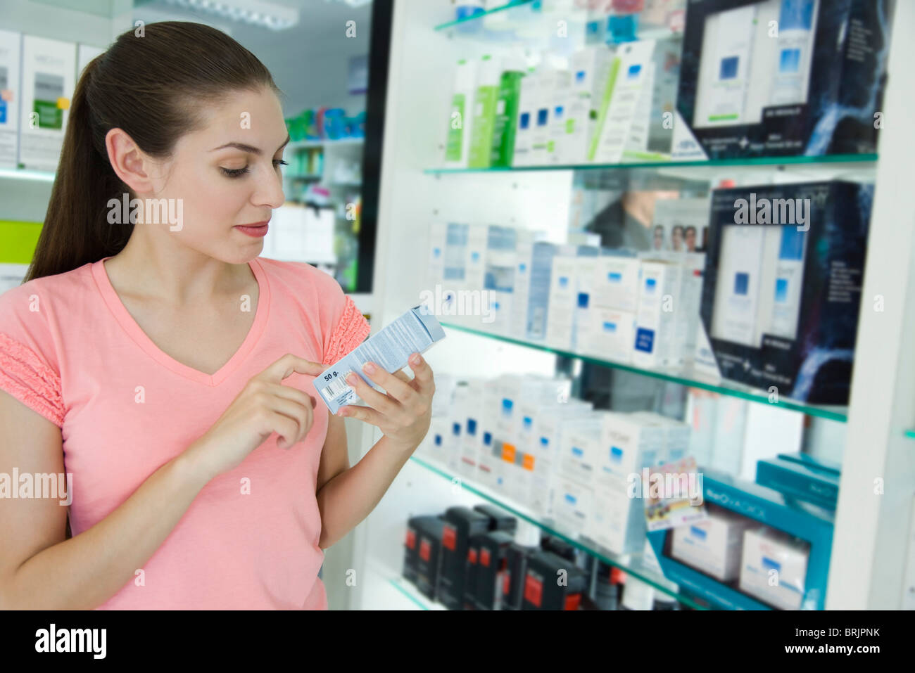 Young woman looking at cosmetics in store - Stock Image