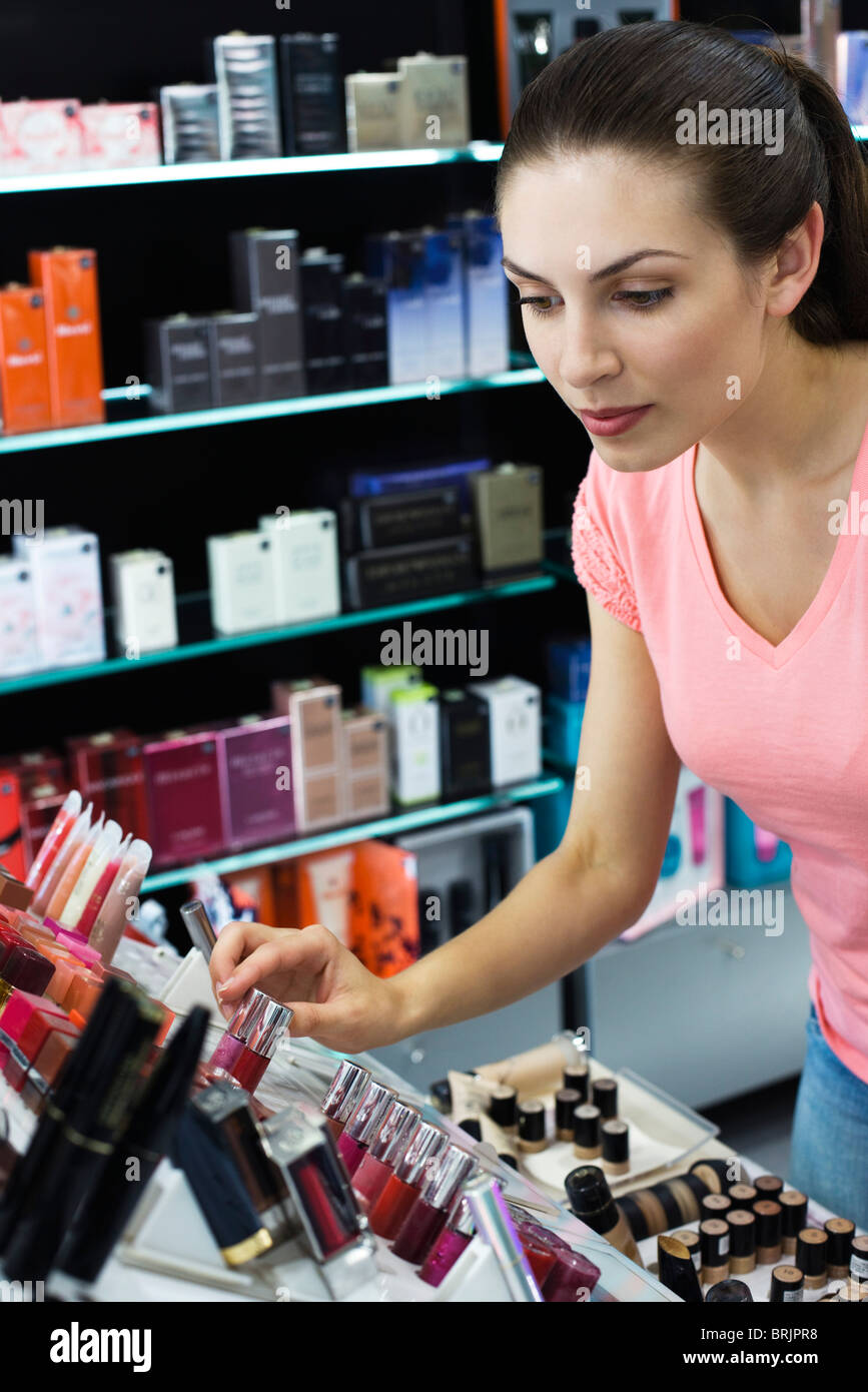 Young woman browsing cosmetics in store - Stock Image