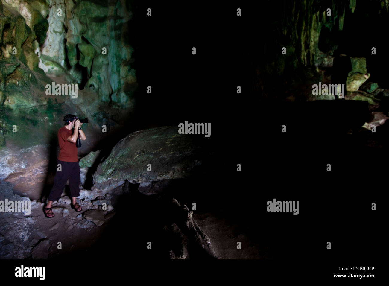 Male photographer shooting a darkened subject in a limestone cave in Thailand. - Stock Image