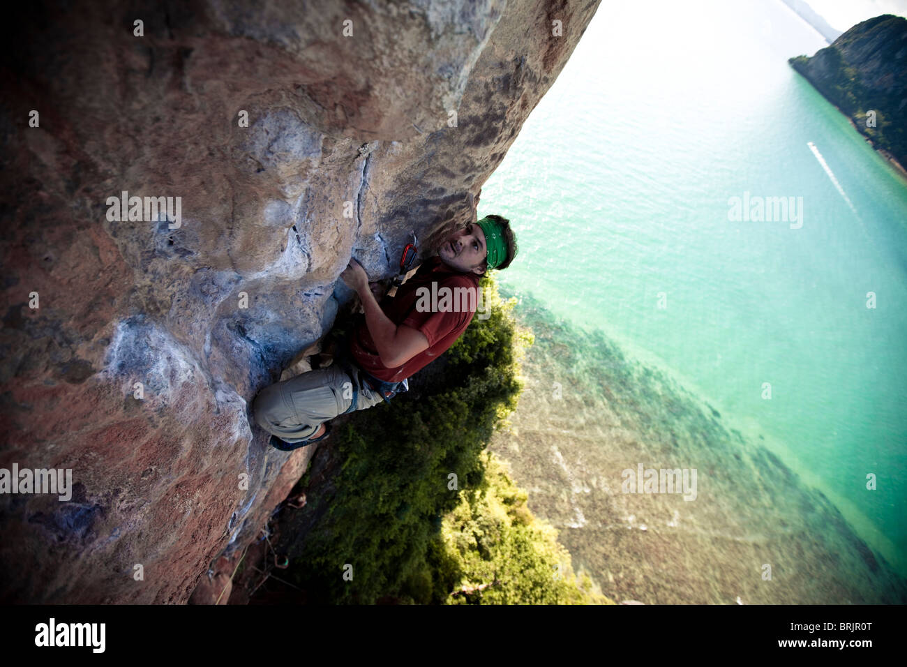 Strained male climber looks to his next move on a limestone beach cliff in Thailand. - Stock Image