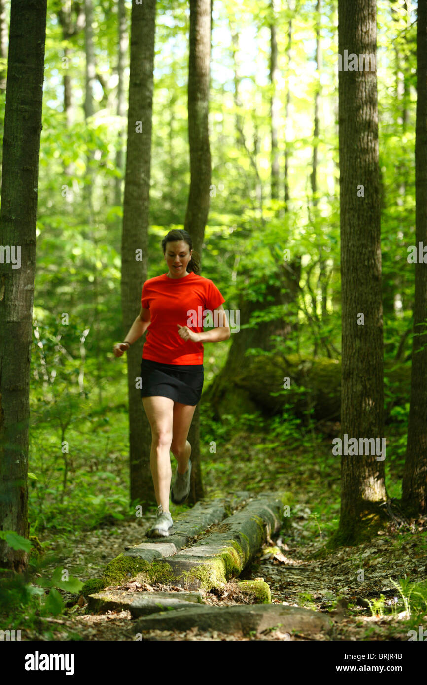 Woman trail running in a lush green forest. - Stock Image