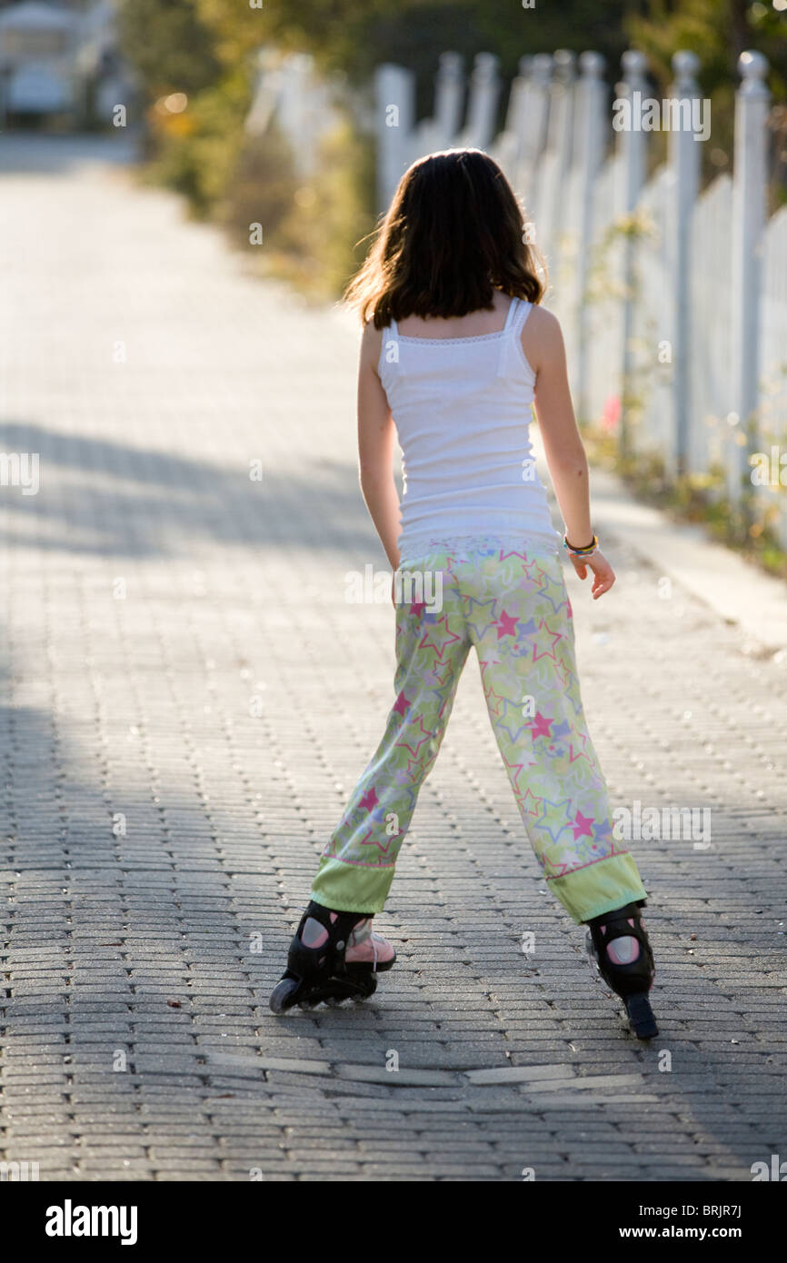 A young girl is roller blading down an alley with a picket fence in the background. - Stock Image